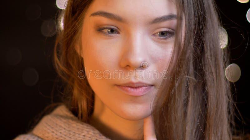 Retrato do close up da fêmea caucasiano atrativa nova com o cabelo moreno que é pensativo no projeto com bokeh fotos de stock royalty free
