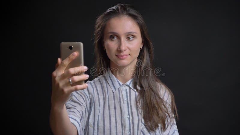 Retrato do close up da fêmea caucasiano bonita nova que toma selfies no telefone e que levanta na frente da câmera com imagem de stock royalty free