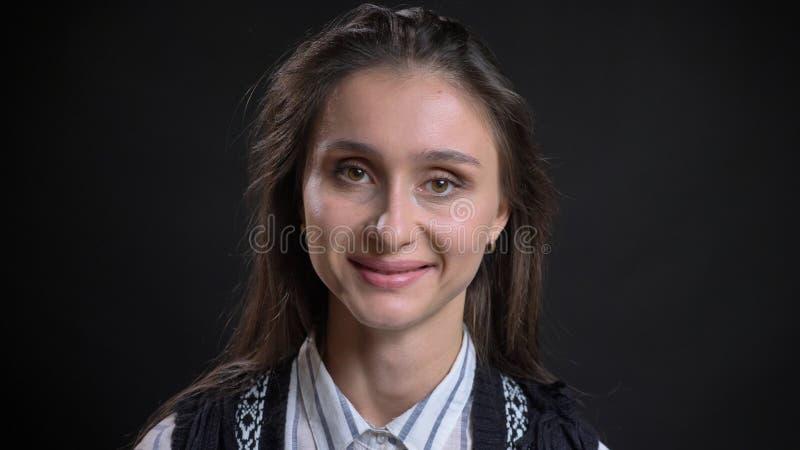 Retrato do close up da fêmea caucasiano bonito nova com o cabelo moreno que olha em linha reta na câmera e que sorri felizmente c imagens de stock royalty free