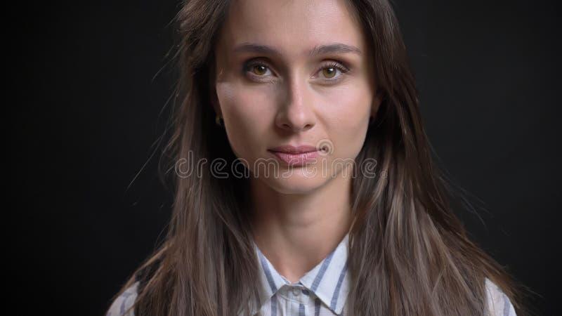 Retrato do close up da fêmea caucasiano bonito nova com o cabelo moreno que olha em linha reta na câmera com facial impassível imagens de stock royalty free
