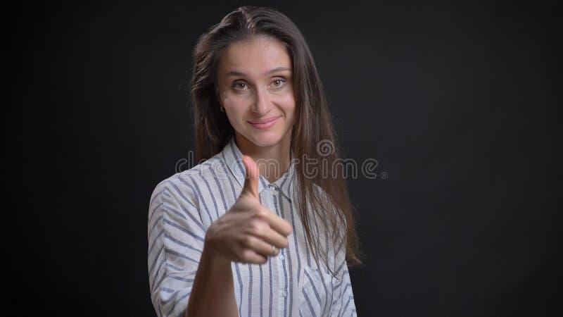 Retrato do close up da fêmea caucasiano bonito nova com o polegar moreno da exibição do cabelo acima e sorrindo alegremente ao ol fotografia de stock