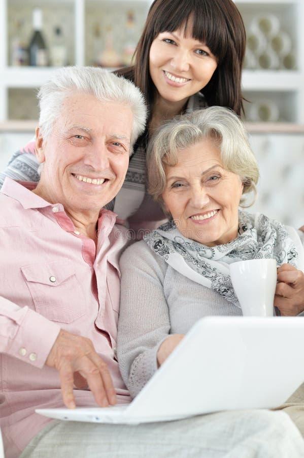 Retrato do close-up da família feliz com portátil em casa fotografia de stock royalty free