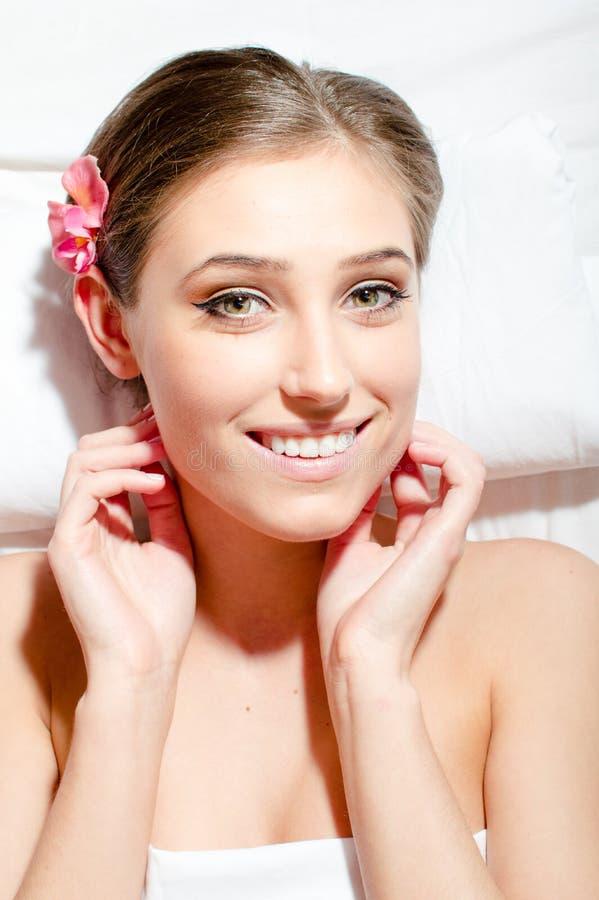Retrato do close up da jovem mulher bonita durante a câmera dos tratamentos sorriso feliz & vista dos termas no branco fotografia de stock royalty free