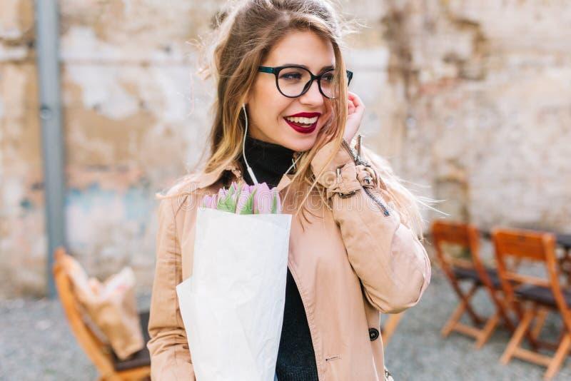 Retrato do close-up da jovem mulher bonita na data no café exterior que guarda flores bonitas Menina de encantamento com foto de stock royalty free