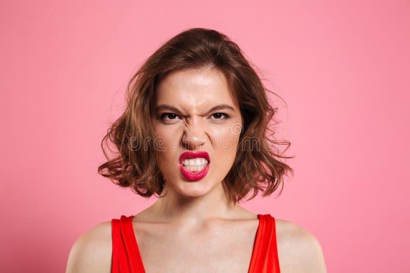Retrato do close-up da jovem mulher irritada com os bordos vermelhos que olham foto de stock
