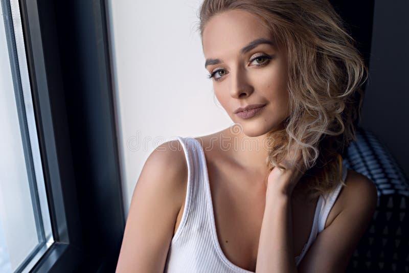Retrato do close-up da jovem mulher moreno lindo assento ao lado da janela Toca em seu cabelo ondulado fotografia de stock