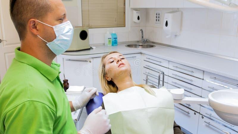 Retrato do close up da jovem mulher que sente o assento assustado na cadeira do dentista imagem de stock