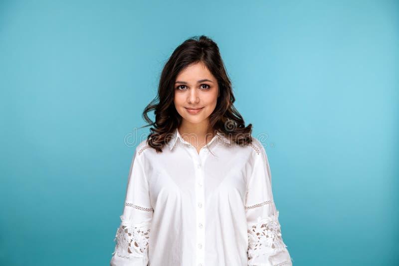 Retrato do close up da menina bonita moreno em uma blusa branca isolada sobre o fundo azul imagens de stock