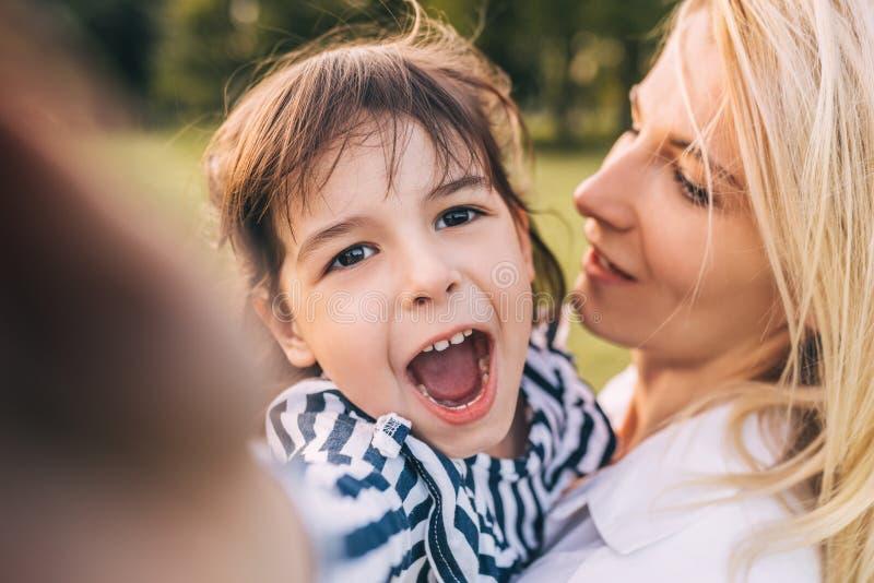 Retrato do close up da menina bonito feliz que olha à câmera que abraça sua mãe no parque Matriz e filha Loving fotos de stock