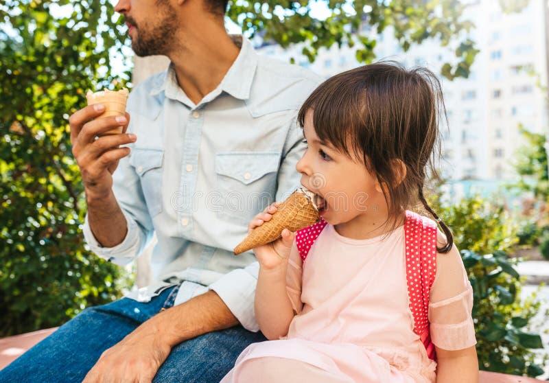 Retrato do close up da menina bonito feliz que senta-se com o paizinho na rua da cidade e que come o gelado exterior Criança da m imagem de stock royalty free