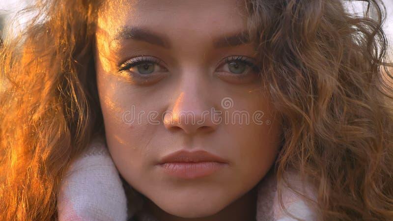 Retrato do close-up da menina caucasiano consideravelmente encaracolado-de cabelo que olha seriamente na câmera no parque outonal imagem de stock royalty free