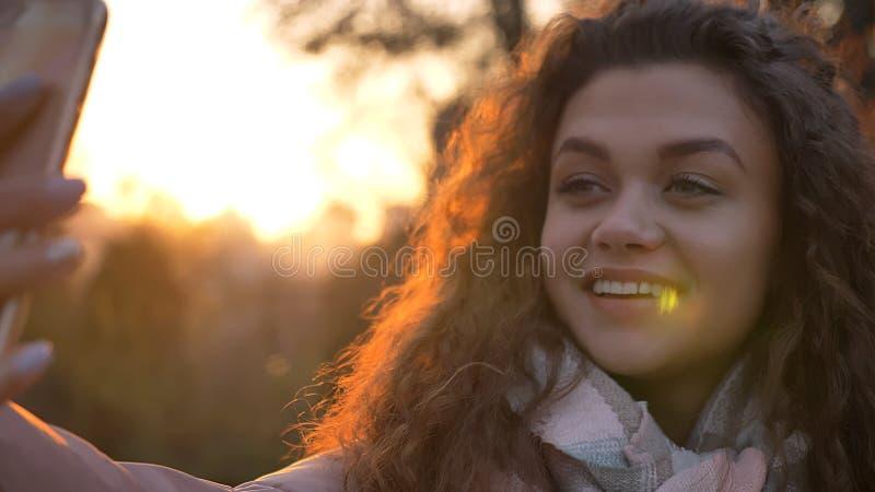 Retrato do close-up da menina caucasiano encaracolado-de cabelo que faz selfie-fotos usando o smartphone no parque outonal imagens de stock royalty free