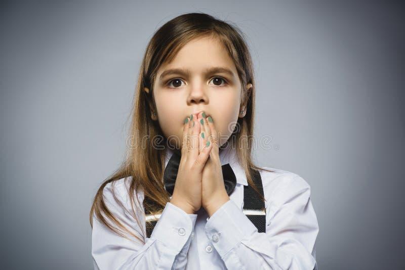 Retrato do close up da menina considerável com expressão surpreendida ao estar contra o fundo cinzento fotografia de stock
