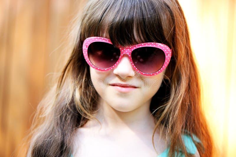 Retrato do Close-up da menina da criança em óculos de sol cor-de-rosa fotos de stock