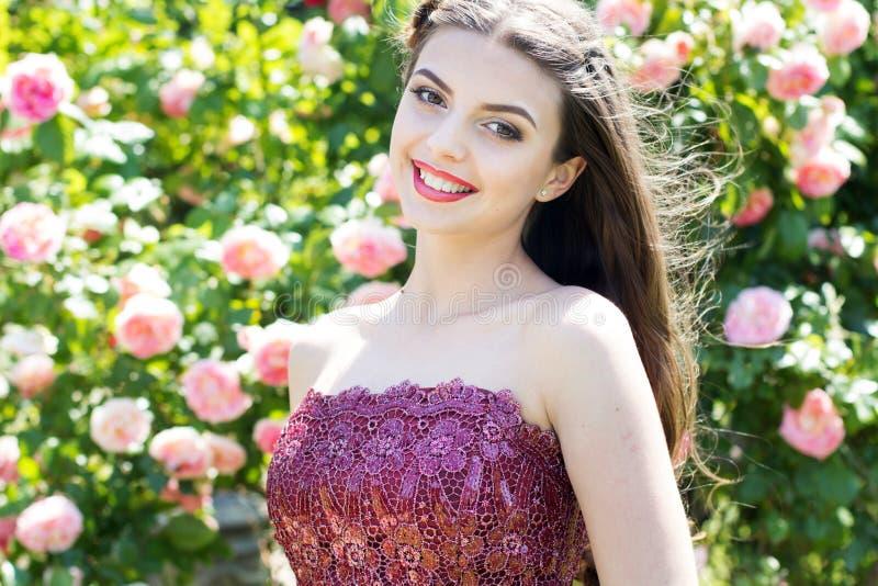 Retrato do close up da menina de sorriso perto das rosas cor-de-rosa foto de stock