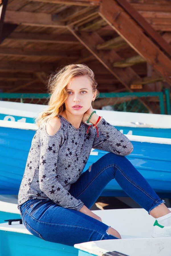 Retrato do close up da menina loura nova bonita nas calças de brim e nas sapatilhas que sentam-se no barco azul na praia fotos de stock royalty free
