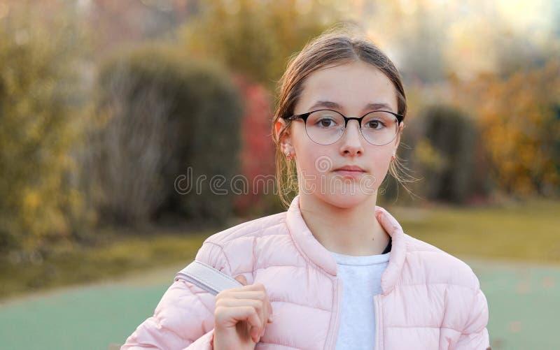 Retrato do close-up da menina preteen bonita em vidros da forma com expressão séria da cara fora no parque do outono imagem de stock