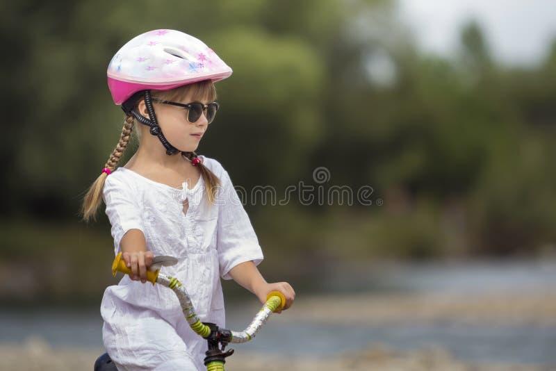 Retrato do close-up da moça bonita orgulhosa na roupa branca, óculos de sol com as tranças louras longas que vestem o ridin cor-d imagem de stock royalty free
