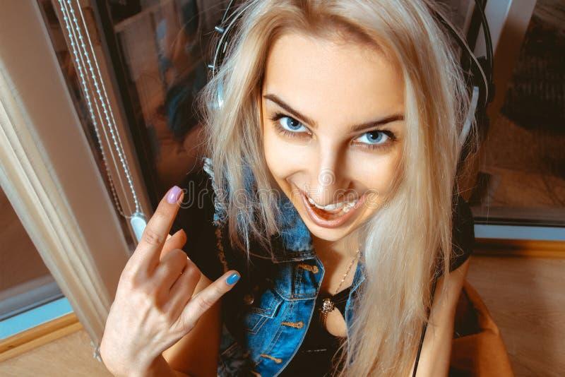 Retrato do close up da moça do divertimento nos fones de ouvido e no sorriso sobre imagem de stock royalty free