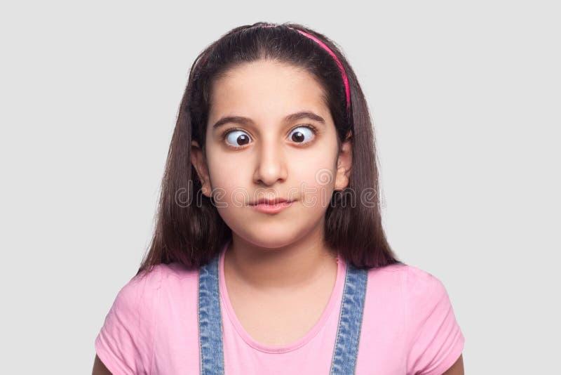 Retrato do close up da moça moreno engraçada louca no estilo ocasional, no t-shirt cor-de-rosa e nos macacões azuis da sarja de N foto de stock royalty free
