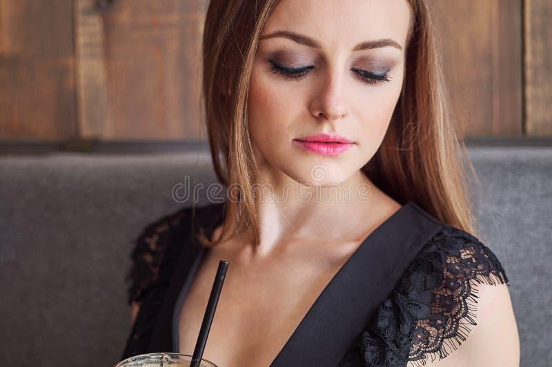 Retrato do close up da mulher adorável nova com composição na moda dos olhos lindos que bebe a xícara de café de vidro grande com fotografia de stock