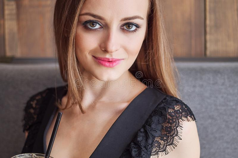 Retrato do close up da mulher adorável nova com composição na moda dos olhos lindos que bebe a xícara de café de vidro grande com fotografia de stock royalty free