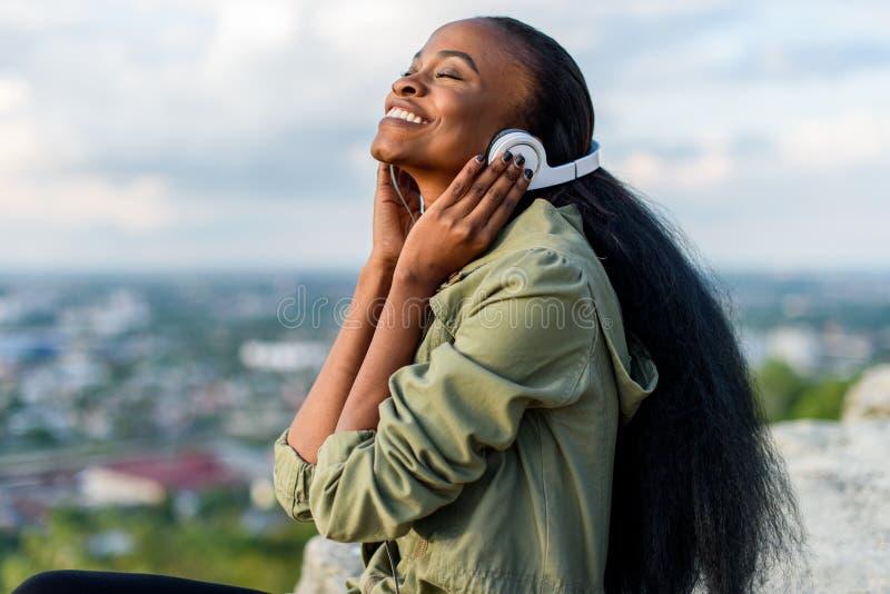 Retrato do close-up da mulher americana de sorriso feliz do africano negro novo que escuta a música Arquitetura da cidade borrada fotografia de stock royalty free