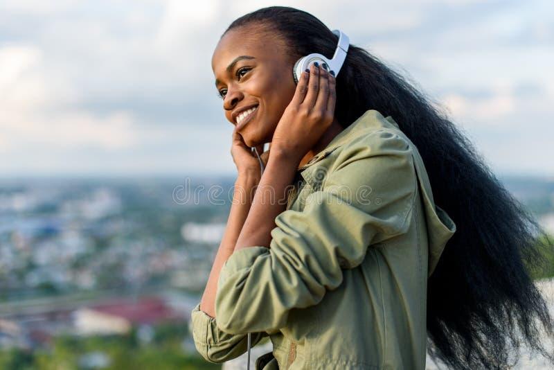 Retrato do close-up da mulher americana do africano negro novo lindo que escuta a música Arquitetura da cidade borrada no fundo fotos de stock