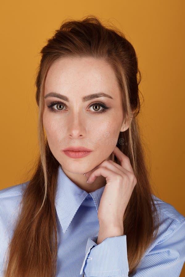 Retrato do close up da mulher bonita de Yong com composi??o brilhante em um est?dio sobre o fundo amarelo fotografia de stock