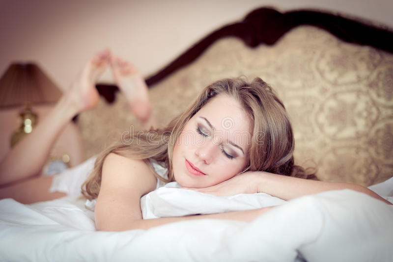 Retrato do close up da mulher bonita nova que tem o encontro fechado de relaxamento dos olhos do divertimento nos pijamas na cama fotografia de stock