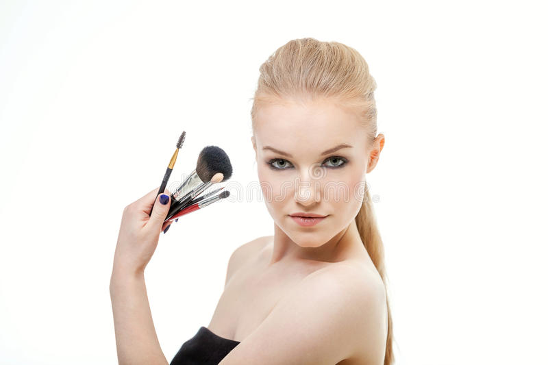 Retrato do close up da mulher com a escova da composição perto da cara imagem de stock royalty free