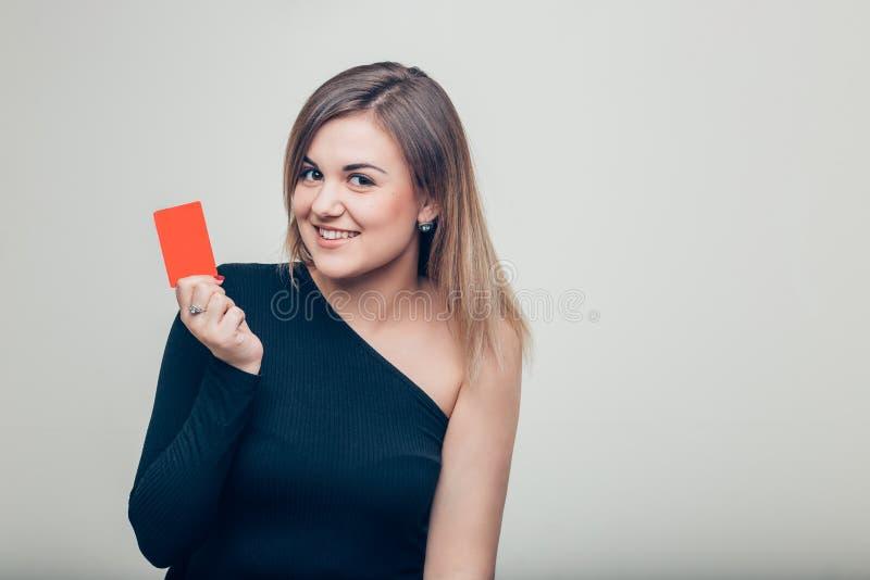 Retrato do close-up da mulher de negócio de sorriso nova que guarda o cartão de crédito imagem de stock royalty free