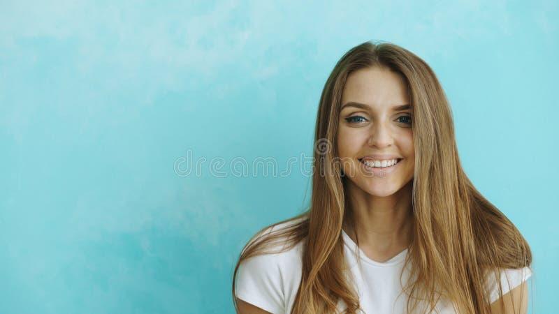 Retrato do close up da mulher de sorriso e de riso nova que olha na câmera no fundo azul imagens de stock