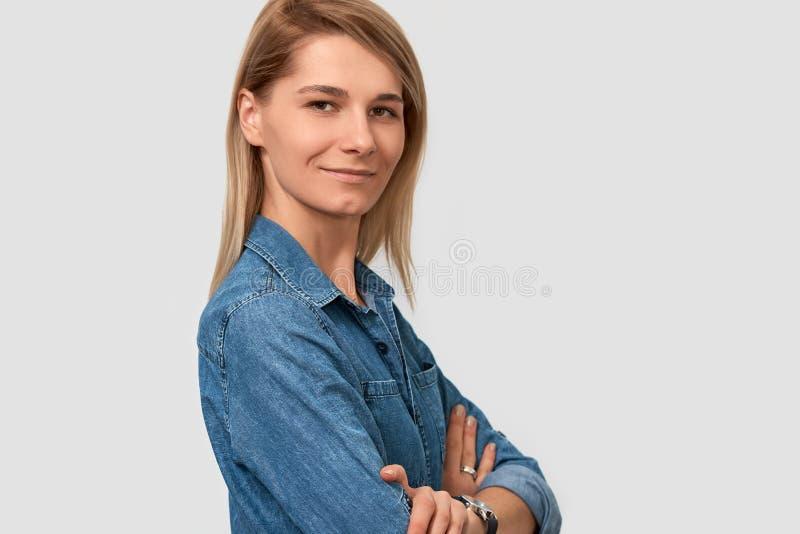Retrato do close up da mulher de sorriso europeia adorável com posição loura do penteado na camisa azul da sarja de Nimes sobre o fotografia de stock royalty free