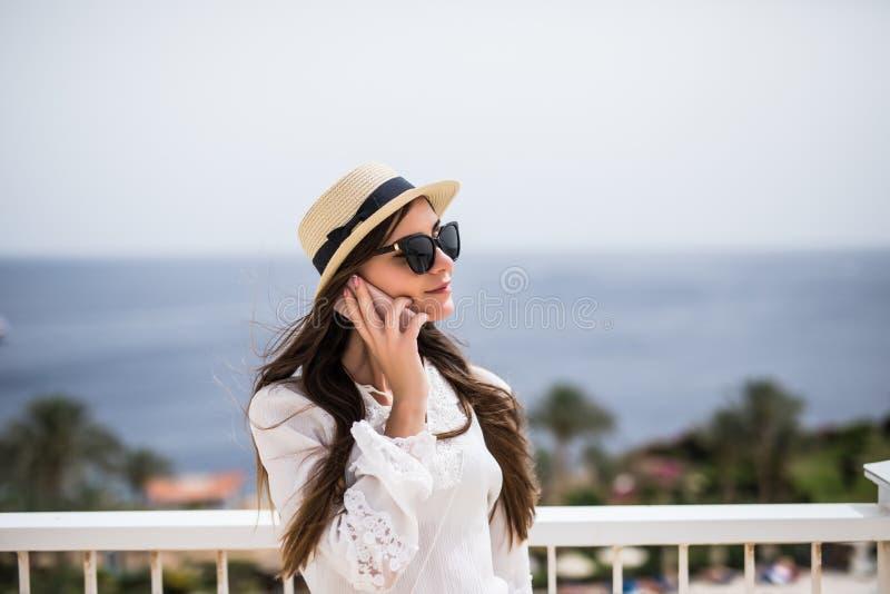 Retrato do close-up da mulher de sorriso que está pela casa de praia e que faz a chamada durante suas férias de verão no fundo do imagens de stock