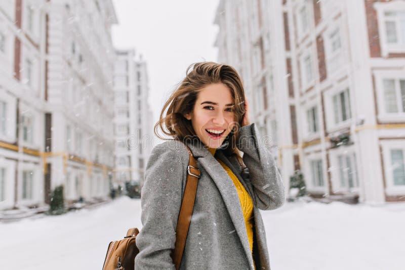 Retrato do close-up da mulher ectática na posição cinzenta elegante do revestimento na rua no dia nevado Foto exterior de imagem de stock royalty free