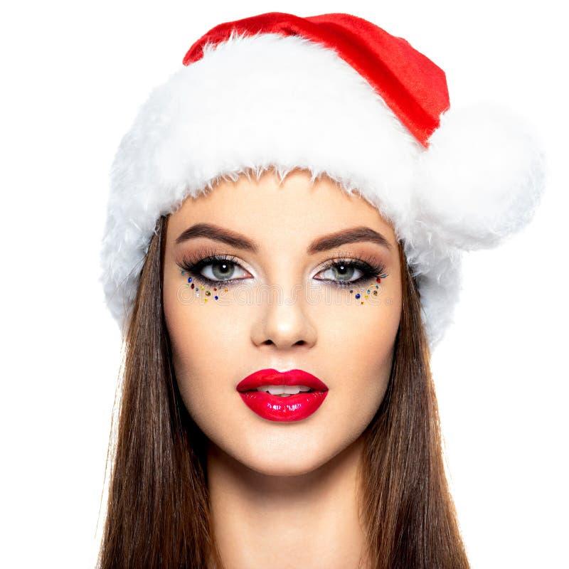 Retrato do close up da mulher em um chapéu de Santa A cara da mulher bonita com composição criativa brilhante imagens de stock