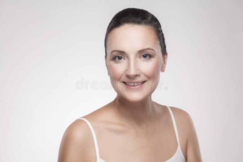 Retrato do close up da mulher encantador, bonita, atrativa com pele perfeita que sorri após o creme, bálsamo, máscara, loção, iso foto de stock