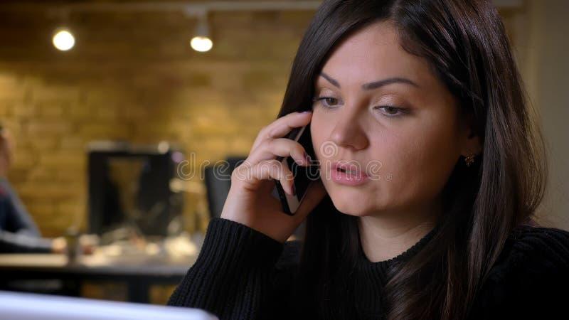 Retrato do close-up da mulher excesso de peso de meia idade na frente do portátil que fala no telefone celular seriamente no fund imagens de stock royalty free