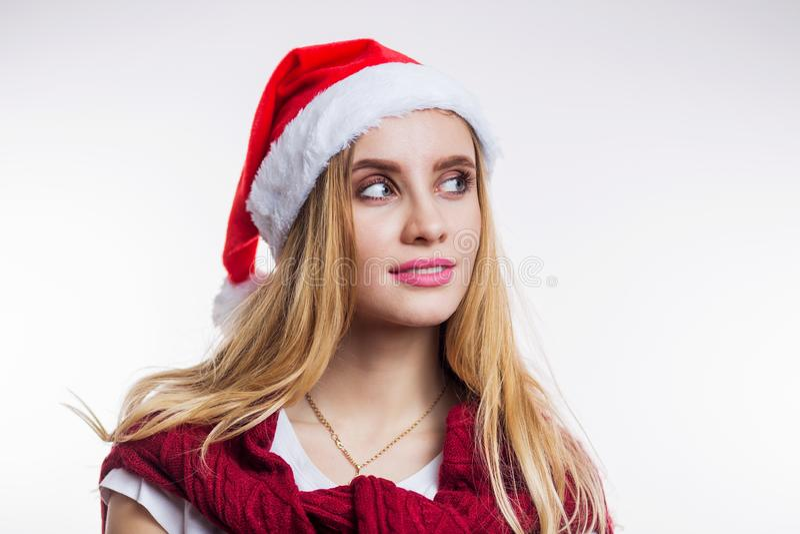 Retrato do close-up da mulher loura de sonho nova que veste o chapéu e a camiseta vermelhos de Santa no fundo branco foto de stock