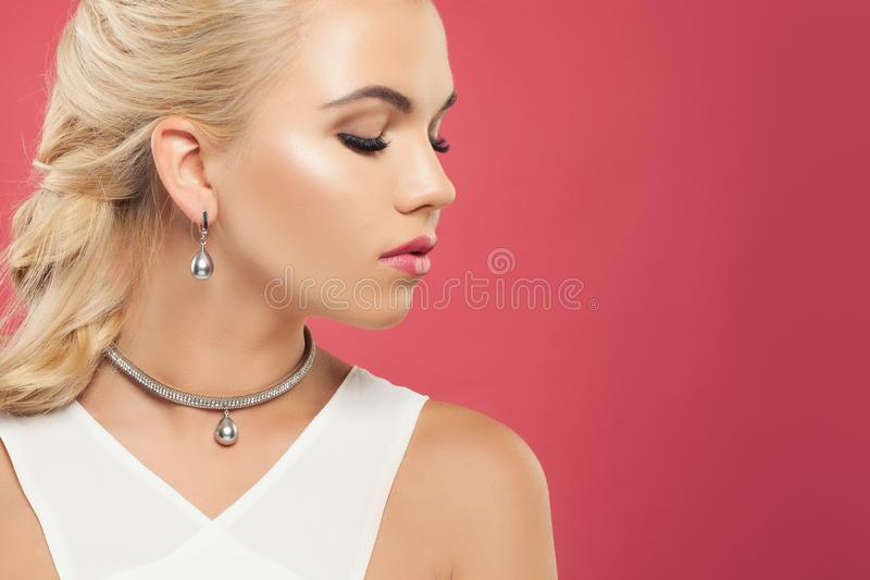 Retrato do close up da mulher loura perfeita com os brincos luxuosos e a colar da joia da platina com diamante e as pérolas preta imagens de stock