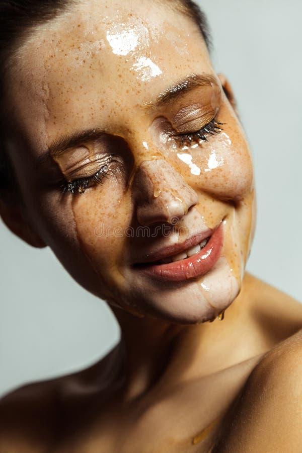 Retrato do close up da mulher moreno nova bonita feliz com sardas e mel na cara com olhos fechados e sorriso toothy foto de stock