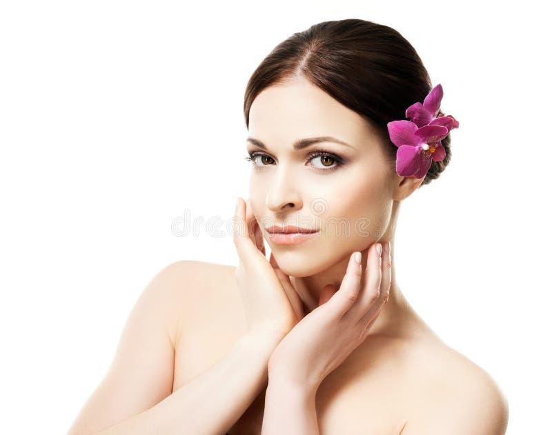 Retrato do close-up da mulher nova, bonita e saudável com uma flor da orquídea em seu cabelo isolado no branco imagem de stock