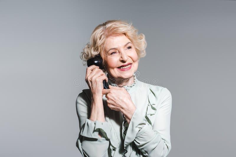 retrato do close-up da mulher superior de sorriso que fala pelo telefone do vintage imagem de stock