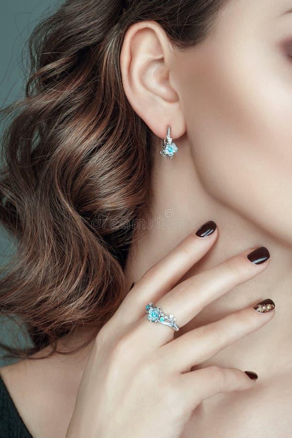 Retrato do close up da orelha e a mão e joia bonita nela Grupo da joia de brincos e de anel com pedra preciosa foto de stock