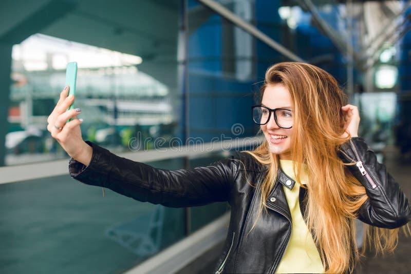 Retrato do close-up da parte externa da posição da moça no aeroporto Tem o cabelo longo, o revestimento preto e os vidros Está fa imagem de stock royalty free