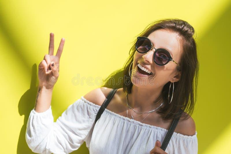 Retrato do close up da posição da menina com sinal de paz na frente da parede verde imagens de stock