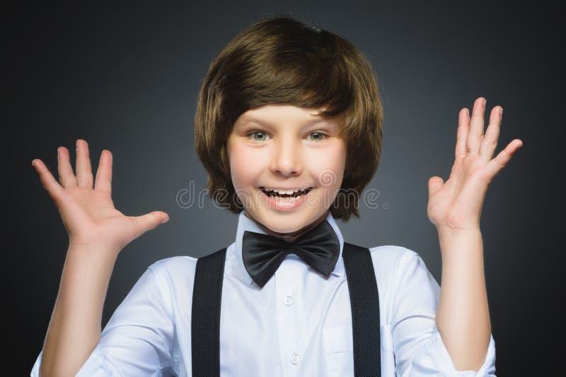 Retrato do close up da surpresa indo do menino feliz isolado no fundo cinzento fotos de stock