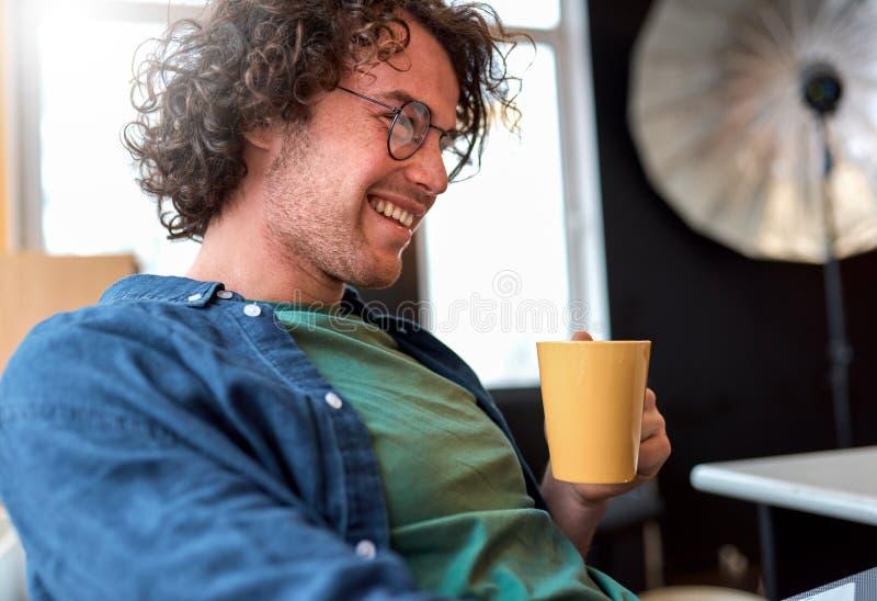 Retrato do close up da vista lateral do freelancer feliz do homem novo que senta-se no escritório que trabalha em um portátil fotografia de stock