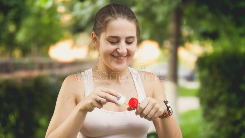 Retrato do close up de bolhas de sabão de sopro de sorriso bonitas da jovem mulher no parque no por do sol imagens de stock royalty free